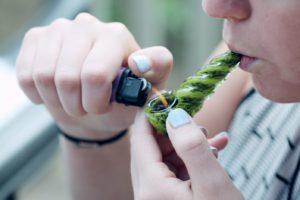 Smoking a glass pipe.